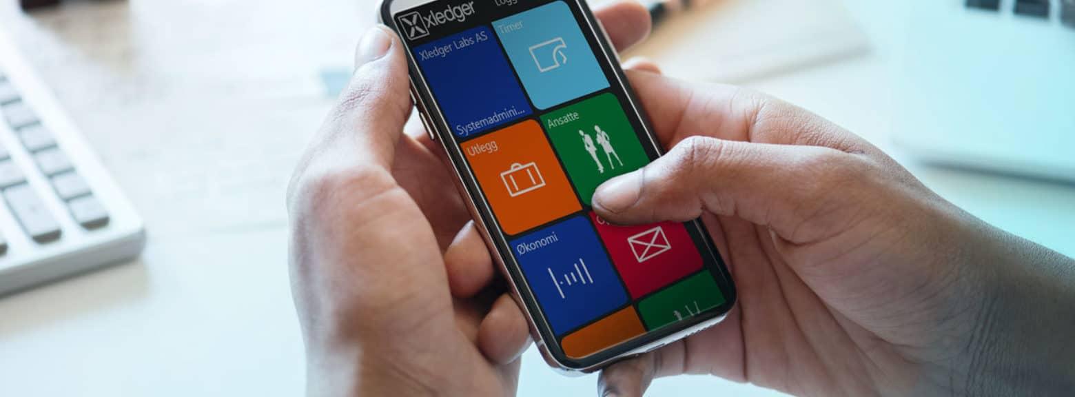 Mann taster på mobil med regnskapssystem