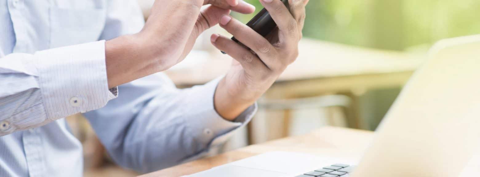 Mann taster på mobil med laptop på bord