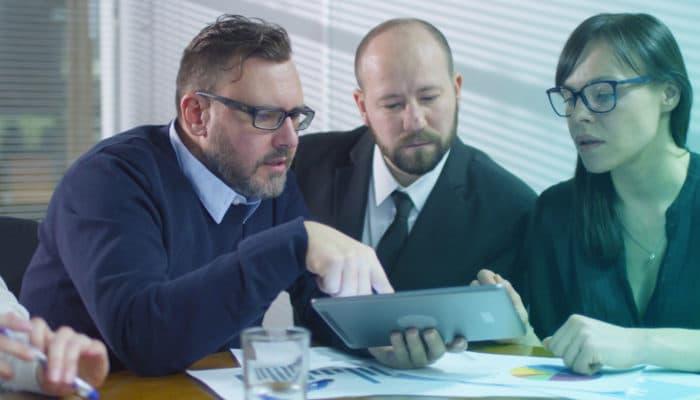 Tre seriøse mennesker diskuterer noe på et nettbrett