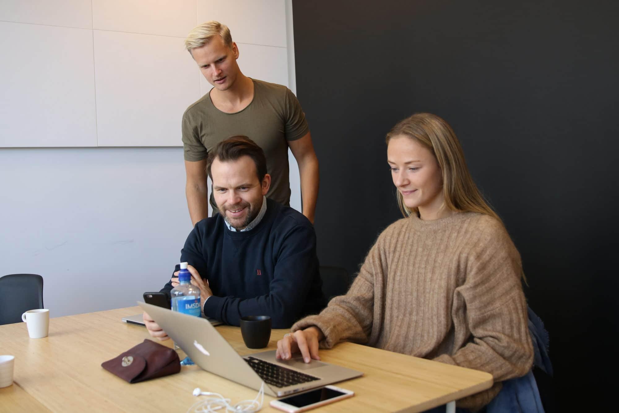 Tre unge mennesker i samtale rundt en laptop