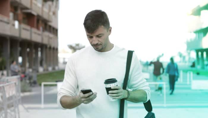 Gående mann med kaffe og smarttelefon
