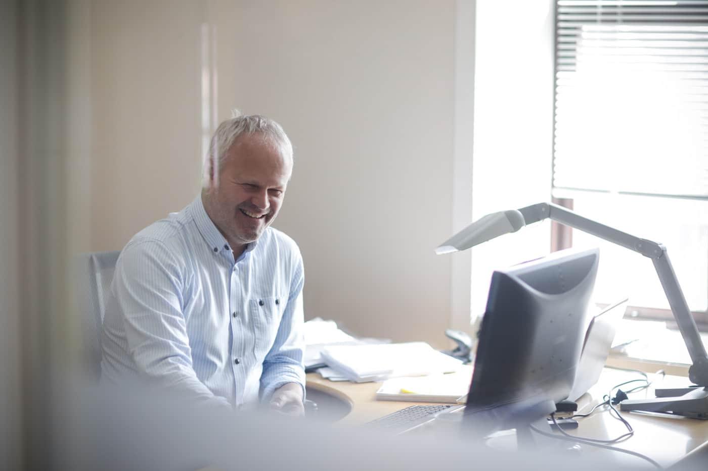 Smilende mann ved sin kontorpult