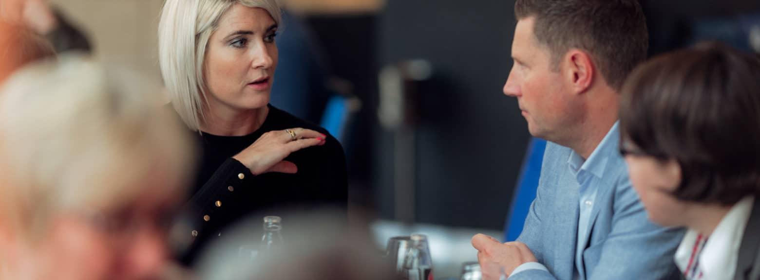 Ung kvinne og ung mann i samtale under en lunsj
