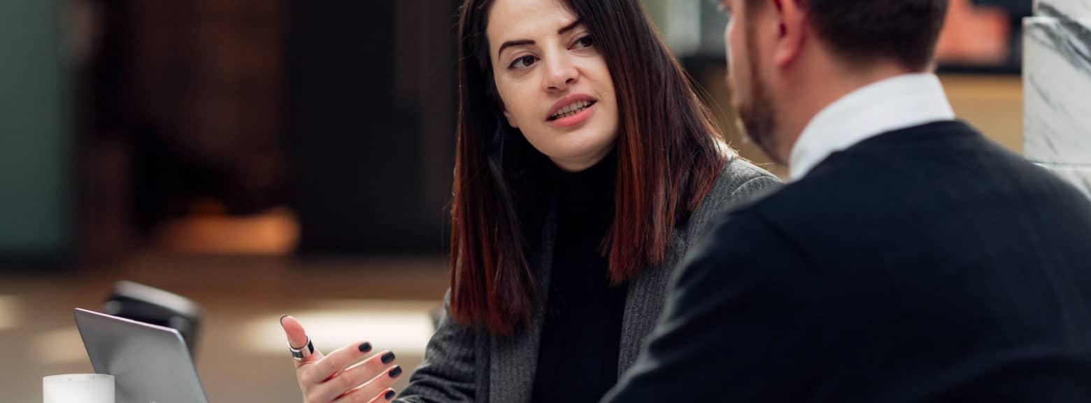 Kvinne og mann i møte over en kaffe