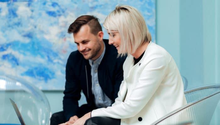 Ung mann og kvinne sitter sammen