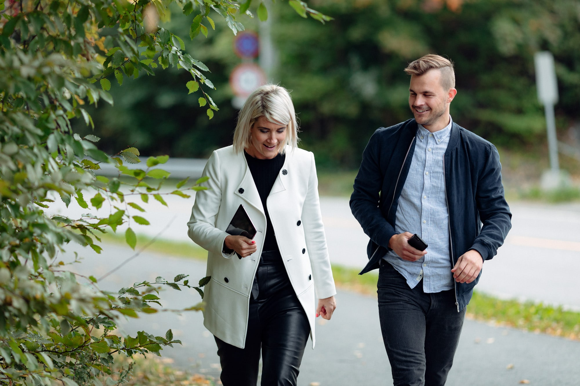 Ung kvinne og ung mann går utendørs og snakker