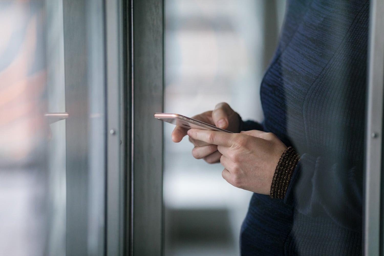 Nærbilde av dame som trykker på en smarttelefon
