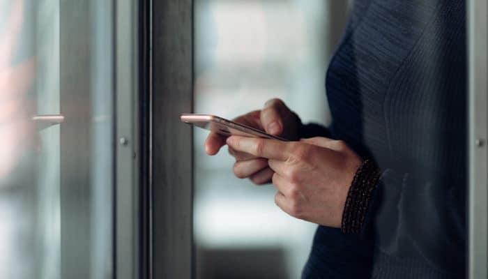 Kvinne taster på mobil ved et vindu