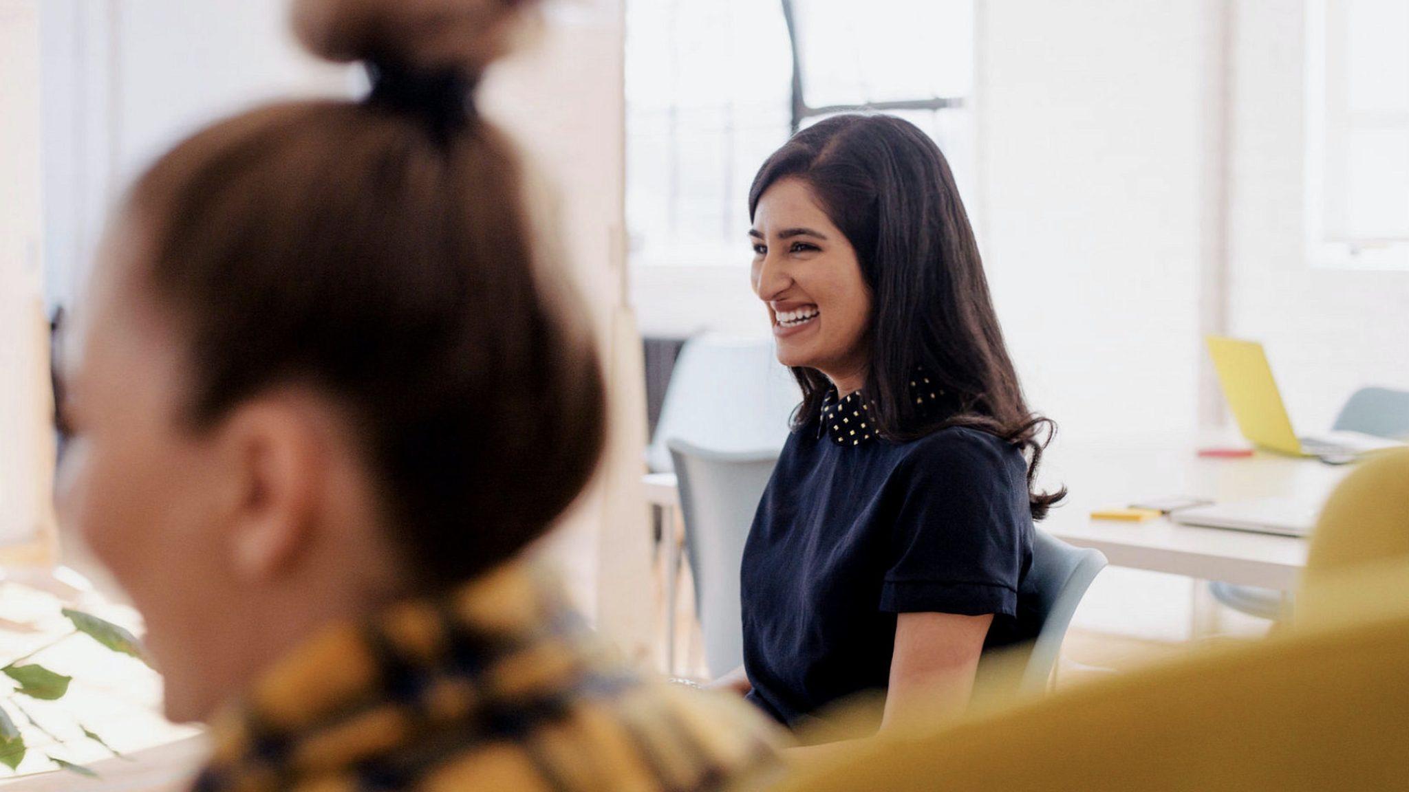 To damer som ler og smiler på kontoret