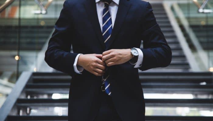 Dresskledd mann som knepper sin jakke