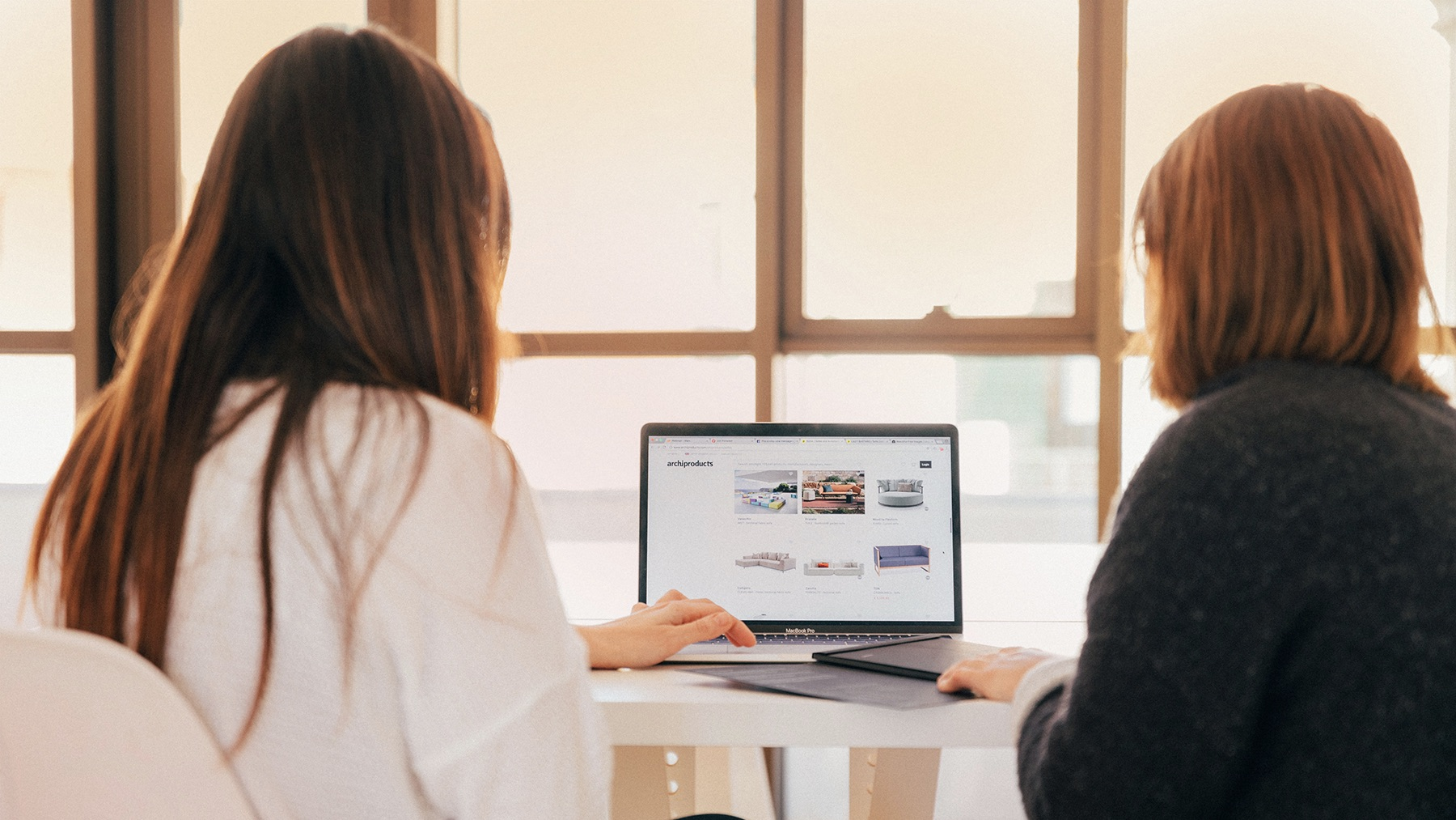 To damer som ser på en laptop