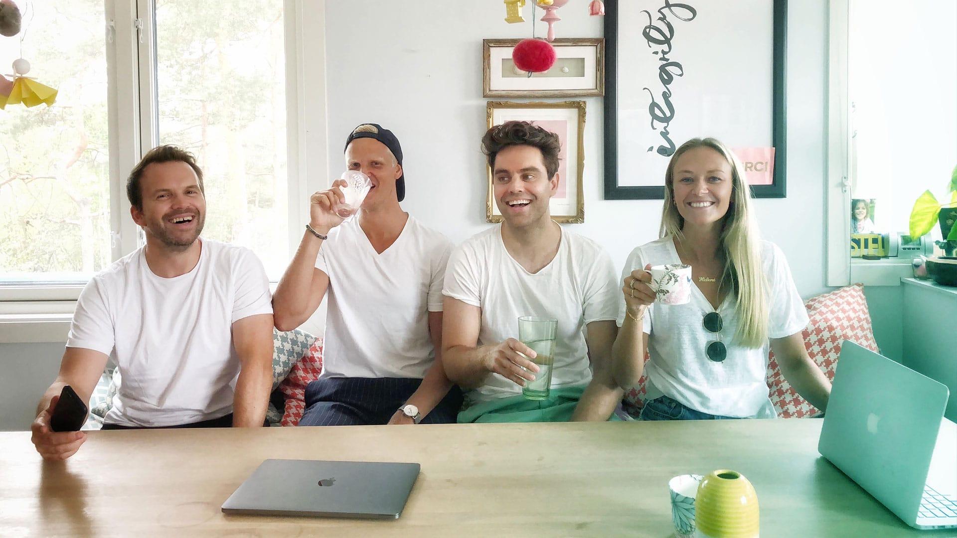 Fire unge voksene smiler sammen i et fargerikt rom