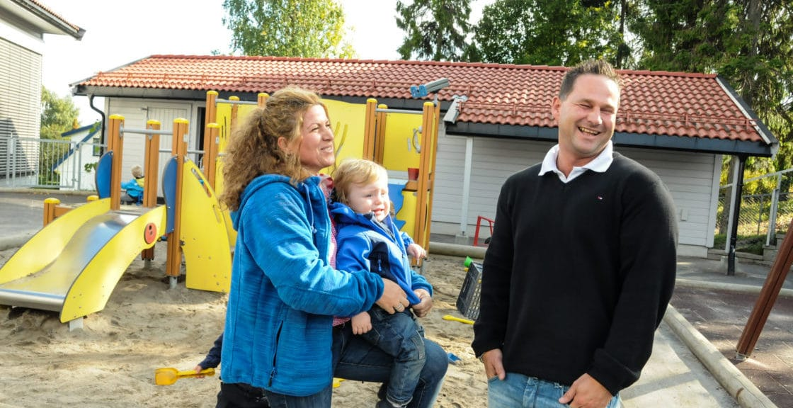 En familie på tre utendørs i en barnehage